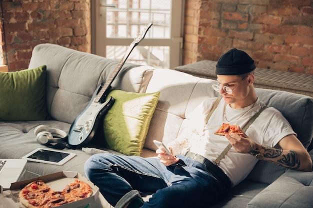 Jedzenie pizzy. mężczyzna uczący się w domu podczas kursów online, inteligentna szkoła. zdobywanie klas lub zawodu w izolacji, kwarantanna przeciwko rozprzestrzenianiu się koronawirusa. korzystanie z laptopa, smartfona, słuchawek.