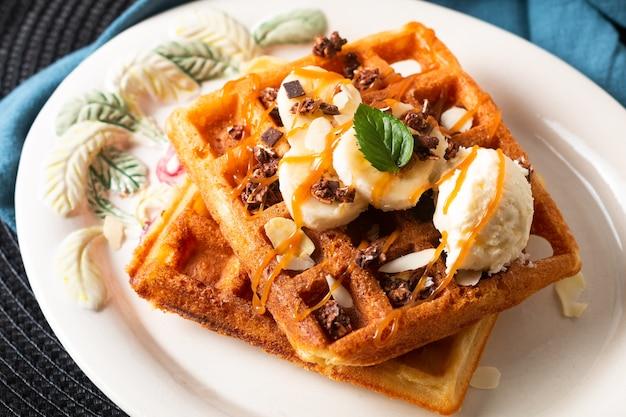 Jedzenie posiłek koncepcja śniadania domowe organiczne gofry bananowo-waniliowe lody z sosem karmelowym na czarnym tle z miejscem na kopię