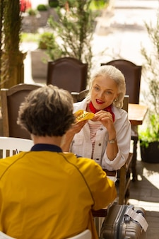 Jedzenie poza domem. szczęśliwy mąż i żona siedzą przy stole naprzeciw siebie jedząc obiad w meksykańskiej restauracji.