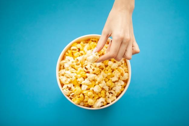 Jedzenie. ręka kobiety, która bierze popcorn z wiadra. wiadro popcorn. kino