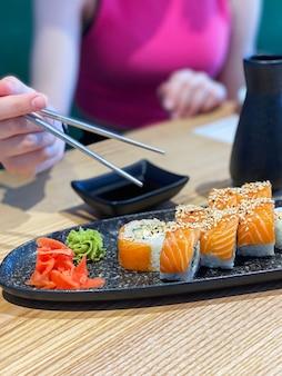 Jedzenie roll sushi w japońskiej restauracji, ręka z pałeczkami