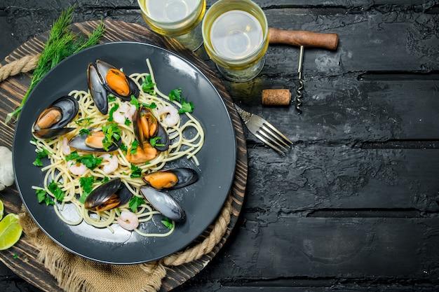 Jedzenie środziemnomorskie. spaghetti z owocami morza z małżami i białym winem na ciemnym rustykalnym stole.