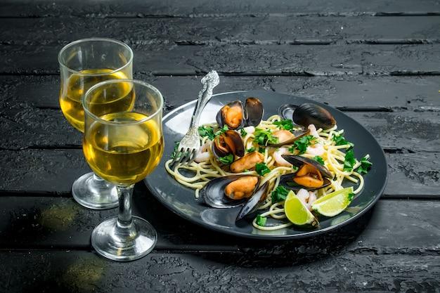 Jedzenie środziemnomorskie. spaghetti z owocami morza z małżami i białym winem. na czarnym rustykalnym.
