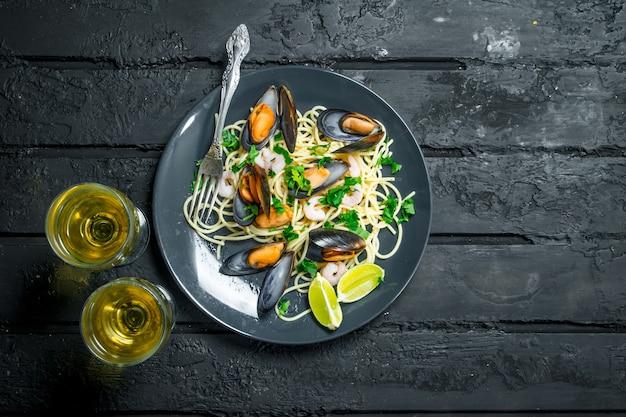 Jedzenie środziemnomorskie. spaghetti z owocami morza z małżami i białym winem. na czarnym tle rustykalnym.