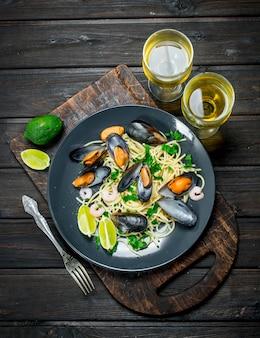 Jedzenie środziemnomorskie. spaghetti z owocami morza z małżami i białym winem. na drewnianym tle.