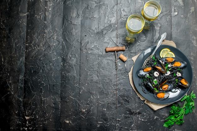 Jedzenie środziemnomorskie. spaghetti z tuszem z mątwy, małżami i białym winem na czarnym rustykalnym stole.