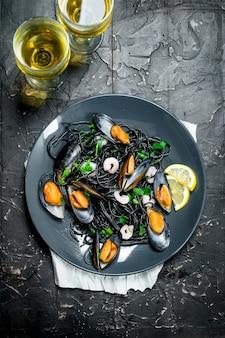 Jedzenie środziemnomorskie. spaghetti z tuszem z mątwy, małżami i białym winem. na czarnym rustykalnym.