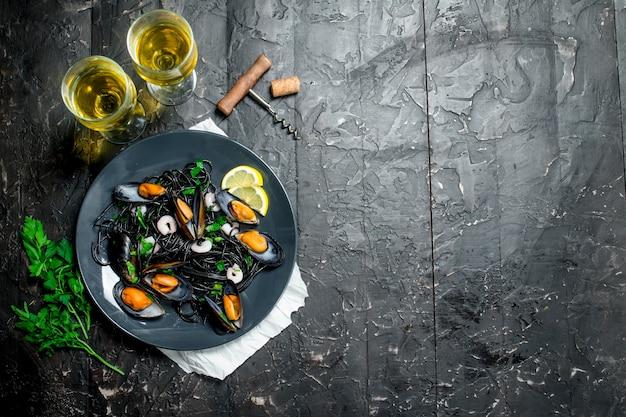 Jedzenie środziemnomorskie. spaghetti z tuszem z mątwy, małżami i białym winem. na czarnym tle rustykalnym.
