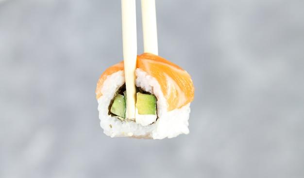 Jedzenie sushi philadelphia roll z bliska pałeczki, japońskie jedzenie sushi roll w restauracji.