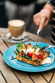 Jedzenie tostów waflowych z jajkiem w koszulce i łososiem z kawą