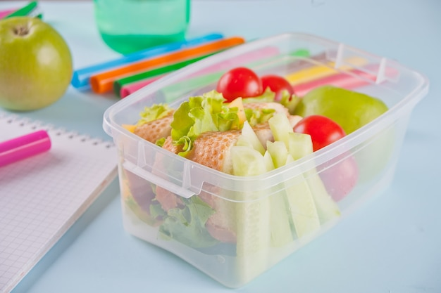 Jedzenie w biurze lub w szkole. pudełko na lunch z jedzeniem na pulpicie.