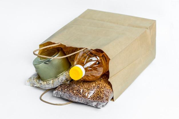 Jedzenie w papierowej torbie na datki, na białym tle. zapas antykryzysowy podstawowych towarów na okres izolacji kwarantanny. dostawa żywności, koronawirus. niedobór jedzenia.