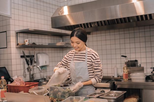 Jedzenie w pojemnikach. ciemnowłosy pomocny pracownik kuchni układający żywność w pojemnikach