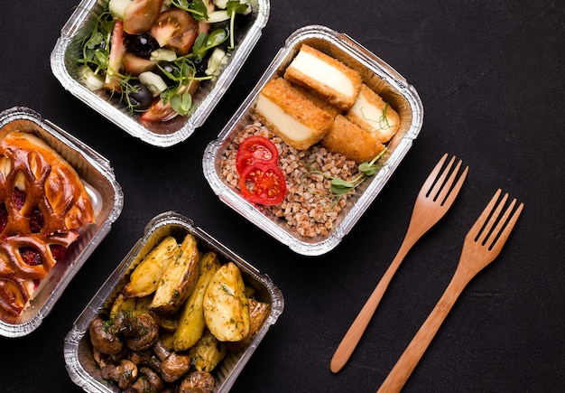 Jedzenie w pojemnikach foliowych obok sztućców.