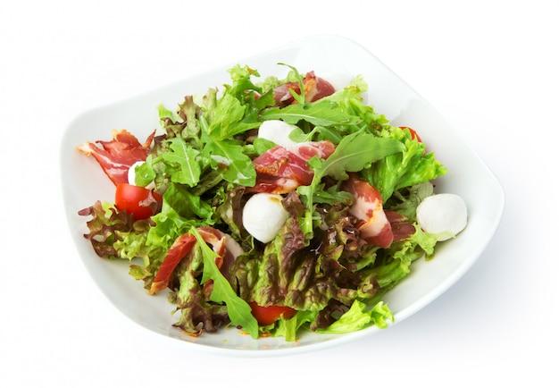 Jedzenie w restauracji na białym tle - sałatka z szynką jamon i mozzarellą