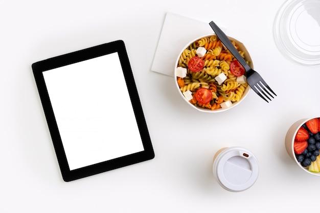 Jedzenie W Zabraniu Pudełka Na Białym Stole Z Tabletem Z Pustym Ekranem Premium Zdjęcia