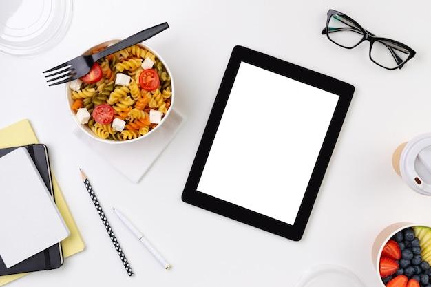 Jedzenie w zabraniu pudełka na białym stole z tabletem z pustym ekranem