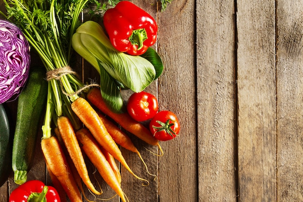 Jedzenie warzywne kolorowe tło. smaczne świeże warzywa na drewnianym stole. widok z góry z przestrzenią do kopiowania.