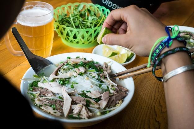 Jedzenie wietnamskiej zupy pho ze świeżą limonką