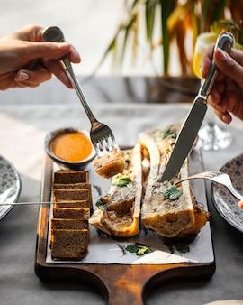 Jedzenie wyśmienitego szpiku kostnego z sosem i chlebem żytnim ze sztućcami