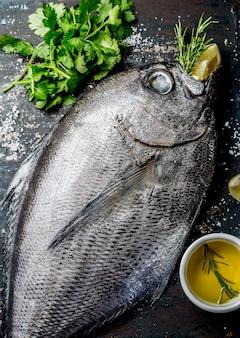Jedzenie z surową świeżą rybą reineta, ziołami, oliwą i cytryną. widok z góry
