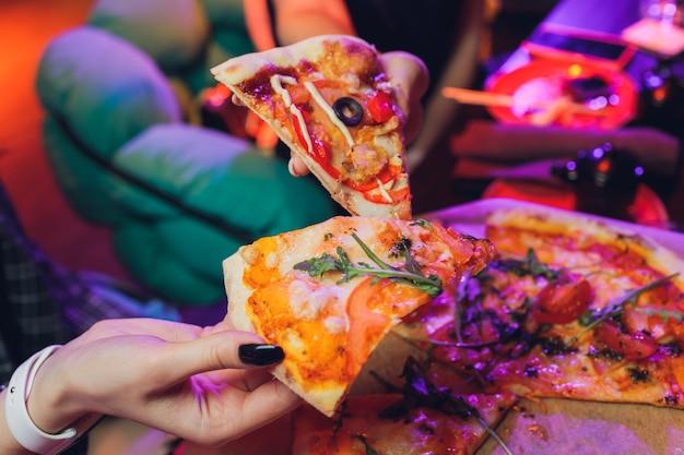 Jedzenie zbliżenie żywności rąk ludzi biorąc plasterki pizzy pepperoni