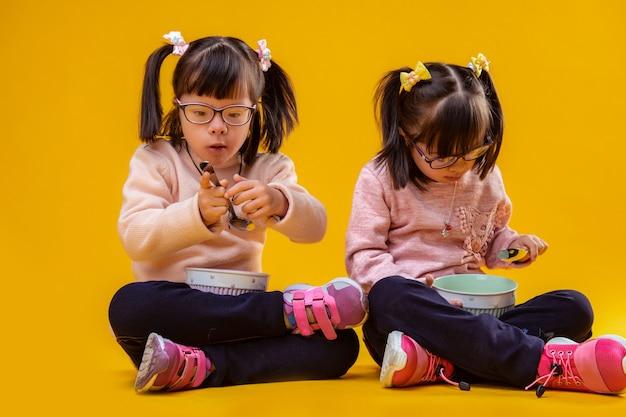 Jedzenie zbóż. dokładne, urocze młode dziewczyny z zespołem downa niosące metalowe łyżeczki i jedzące lekkie śniadanie