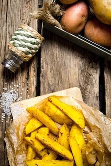 Jedzenie ziemniaczane. frytki z przyprawami i solą na podłoże drewniane