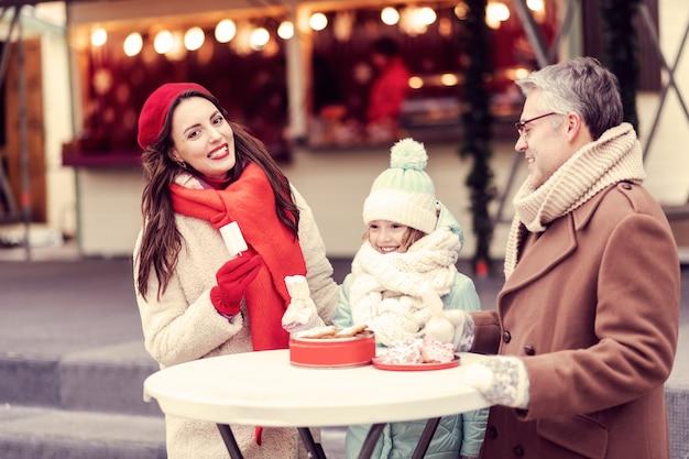 Jedzmy. radosna dziewczyna utrzymująca uśmiech na twarzy, stojąca między rodzicami