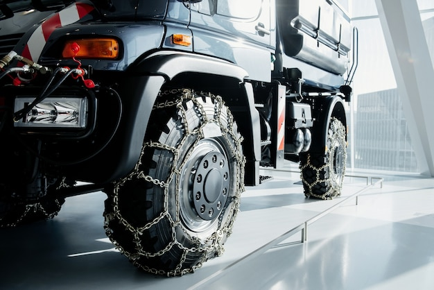 Jeep z łańcuchami śnieżnymi zaparkowany w pomieszczeniu przy białej płytce na pokazie pojazdów.
