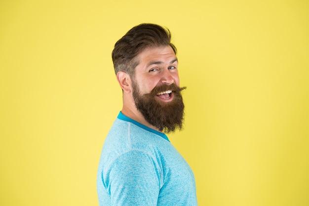 Jego brodate włosy wyglądają na wystylizowane. brodaty mężczyzna uśmiechający się na żółtym tle. szczęśliwy brodaty hipster ze stylową fryzurą. brutalny facet kaukaski nosi wąsy i brodę na twarzy z brodą.