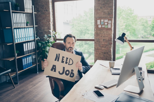 Jego on przygnębiony finanse specjalista ds. sprzedaży ubezpieczeń ekonomista prawnik korporacyjny partner lider facet trzymający w rękach ogłoszenie szukanie pracy na nowoczesnym loftowym ceglanym miejscu pracy przemysłowej