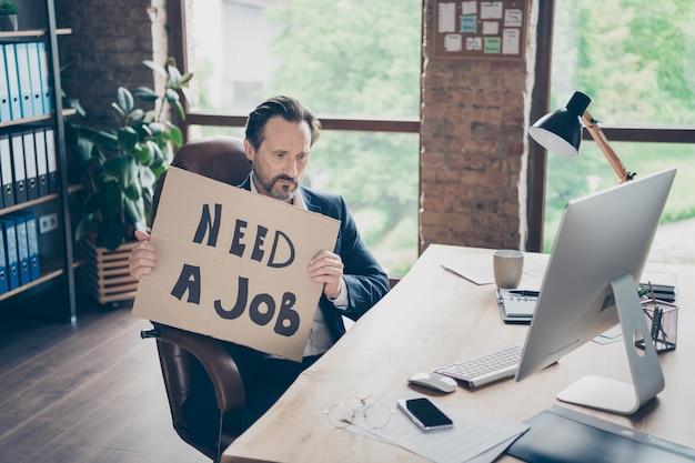 Jego przygnębiony sfrustrowany finanse ubezpieczenie prawnik partner lider specjalista ekspert facet trzymający w rękach ogłoszenie szukający nowej pracy na nowoczesnym loftowym ceglanym miejscu pracy przemysłowej