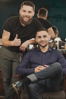 Jego przyjaciel jest fryzjerem. portret szczęśliwy męski klient i jego fryzjer uśmiecha się wesoło i pokazuje kciuki do góry