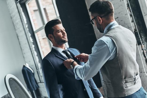 Jego wygląd jest świetny. młody modny projektant pomagający swojemu klientowi się ubrać