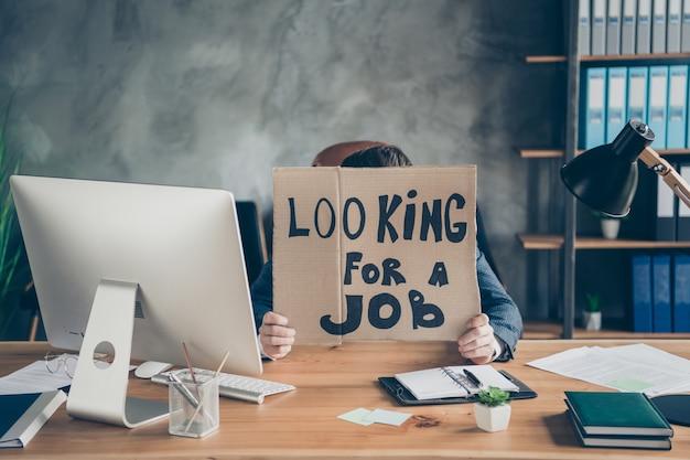 Jego zwolnił przygnębionego agenta pośrednika w handlu nieruchomościami bibliotekarza chowającego się za plakatem promocyjnym szukam pracy ludzka praca antykryzysowy plan niepowodzenie na poddaszu przemysłowa stacja robocza w miejscu pracy