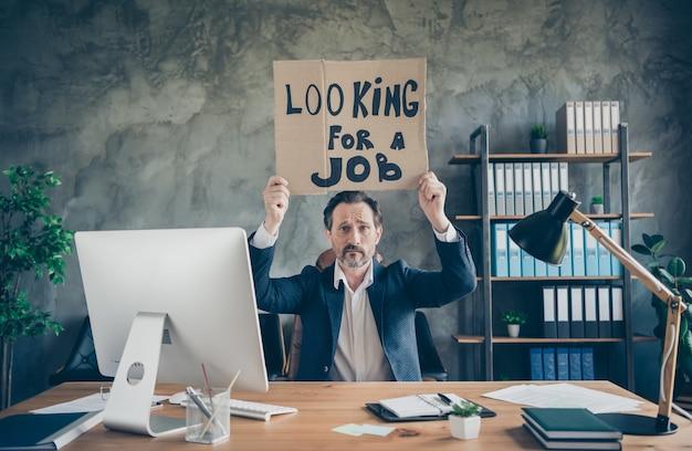 Jego zwolnił przygnębiony nieszczęśliwy agent broker finanse ubezpieczenia wykonawczy specjalista facet trzymający w rękach plakat promocyjny szukający nowej szansy pracy na poddaszu przemysłowe stanowisko pracy