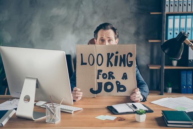 Jego zwolnił zdesperowany agent pośrednik nieruchomości facet trzymający w rękach plakat promocyjny szukam rozmowy kwalifikacyjnej antykryzysowy plan gospodarki na poddaszu przemysłowe stanowisko pracy