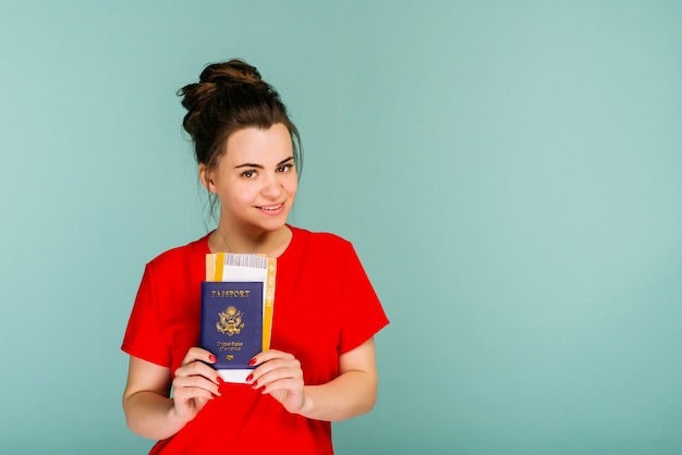 Jej czas na podróż nowoczesna, modna uśmiechnięta kobieta w czerwonej sukience z biletami lotniczymi i paszportem w dłoni