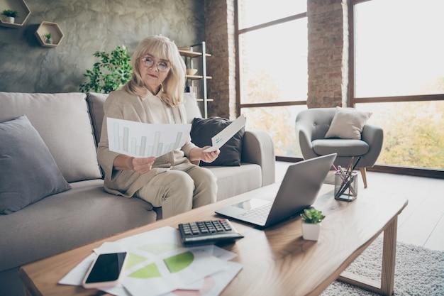 Jej portret jest ładna atrakcyjna, inteligentna, sprytna, skupiona na sobie, siwowłosa biznesmenka siedząca na sofie przygotowująca analizę raportu na poddaszu z cegły przemysłowej mieszkanie w nowoczesnym stylu