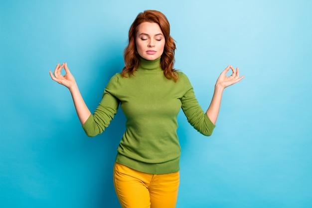 Jej portret jest ładną atrakcyjną pogodną spokojną falistą dziewczyną pokazującą gest om medytujący na białym tle nad jasnym, żywym połyskiem żywy niebieski turkusowy turkusowy kolor ściany