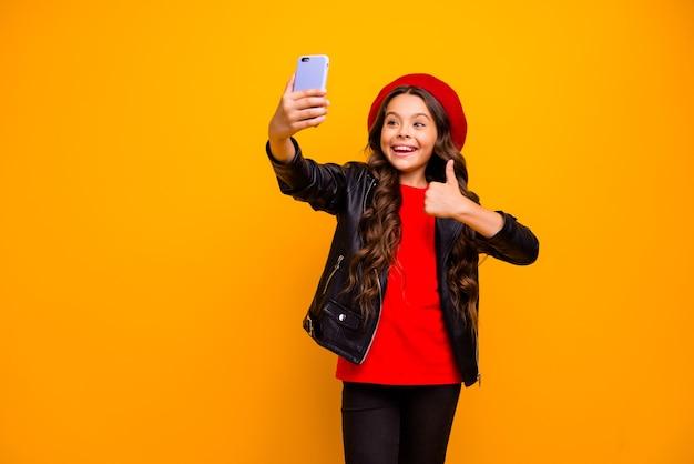 Jej portret jest ładna, atrakcyjna, radosna, wesoła, wesoła, długowłosa dziewczyna robi selfie, pokazując kciuk na blogu na białym tle nad jasnym, żywym połyskiem, żywą żółtą ścianą