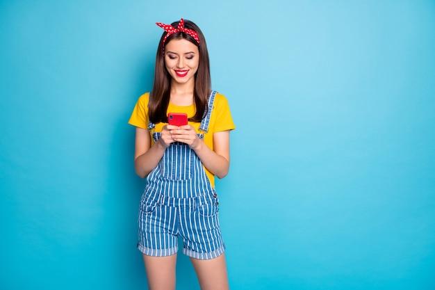 Jej portret jest ładną atrakcyjną uroczą całkiem wesołą dziewczyną trzymającą się w rękach za pomocą usługi wifi komórka na białym tle na jasny, żywy połysk, żywy niebieski zielony turkusowy turkusowy kolor tła