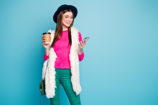 Jej portret jest ładną atrakcyjną wesołą wesołą brązowowłosą dziewczyną za pomocą urządzenia spędzającego wolny czas pijąc latte na białym tle na jasnym, żywym połysku, żywy zielony niebieski turkusowy kolor ściany
