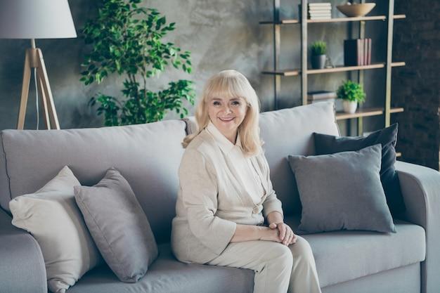 Jej portret jest miła atrakcyjna przyjazna miła wesoła, wesoła, siwowłosa blond babcia w średnim wieku siedzi na sofie odpoczywa ciesząc się emeryturą w mieszkaniu mieszkalnym w domu