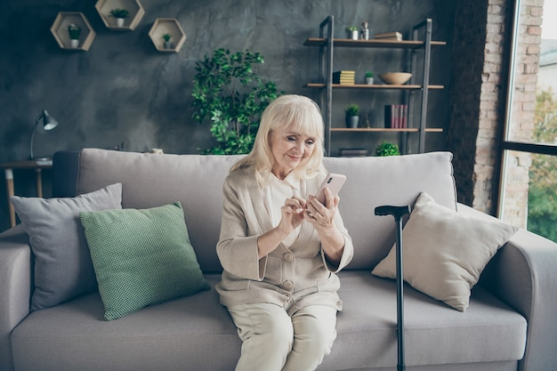 Jej portret jest miła atrakcyjna urocza, wesoła, wesoła, siwowłosa babcia siedzi na sofie i pisze sms do krewnych przejście na emeryturę w industrialnym ceglanym lofcie w nowoczesnym stylu