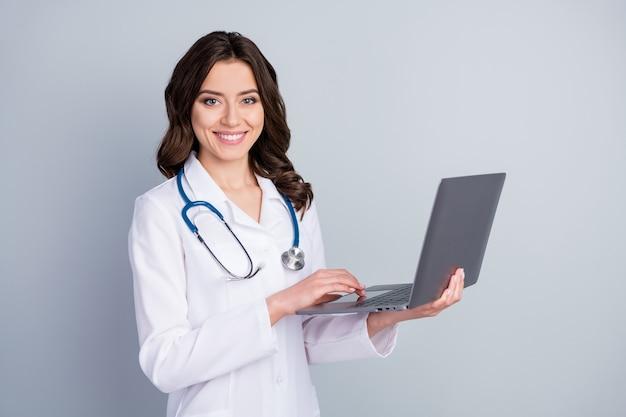 Jej portret ona ładna atrakcyjna, wesoła, falowana dziewczyna doc fonendoskop stetoskop trzyma w rękach laptop niezależny ubezpieczenie medyczne na białym tle na szarym tle w pastelowym kolorze
