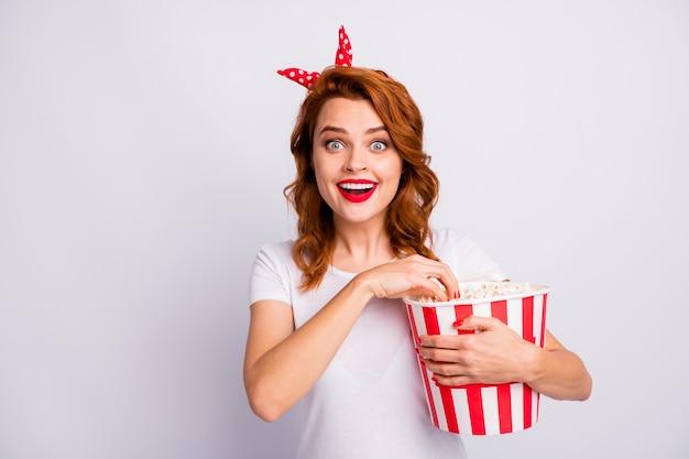 Jej portret z bliska jest ładna atrakcyjna urocza urocza urocza wesoła wesoła radosna zdumiona dziewczyna je kukurydzę widząc nowy komediowy film komediowy odizolowany na jasnobiałej pastelowej ścianie