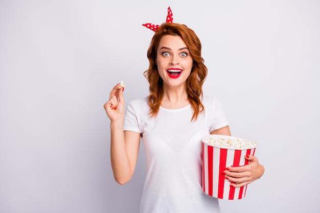 Jej portret z bliska jest ładną atrakcyjną wesołą wesołą podekscytowaną uzależnioną czarującą dziewczyną jedzącą popcorn widząc komedię odizolowaną na jasnobiałej pastelowej ścianie