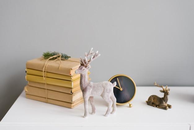 Jeleń bożonarodzeniowy w wystroju na półce z książkami i zegarem